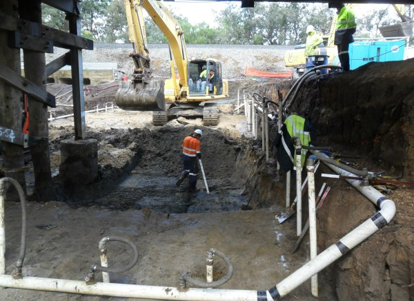 WML Civil Works workers and a large digger excavating the site below the bridge in Western Australia.