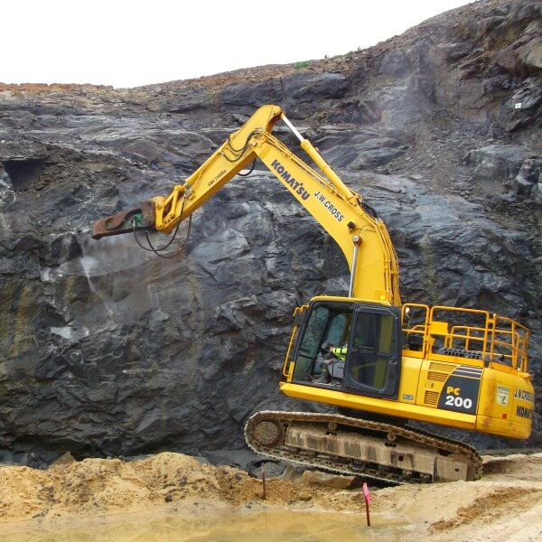 A digger pulling down large rock boulders as part of one of WMLs geotechnical works projects.