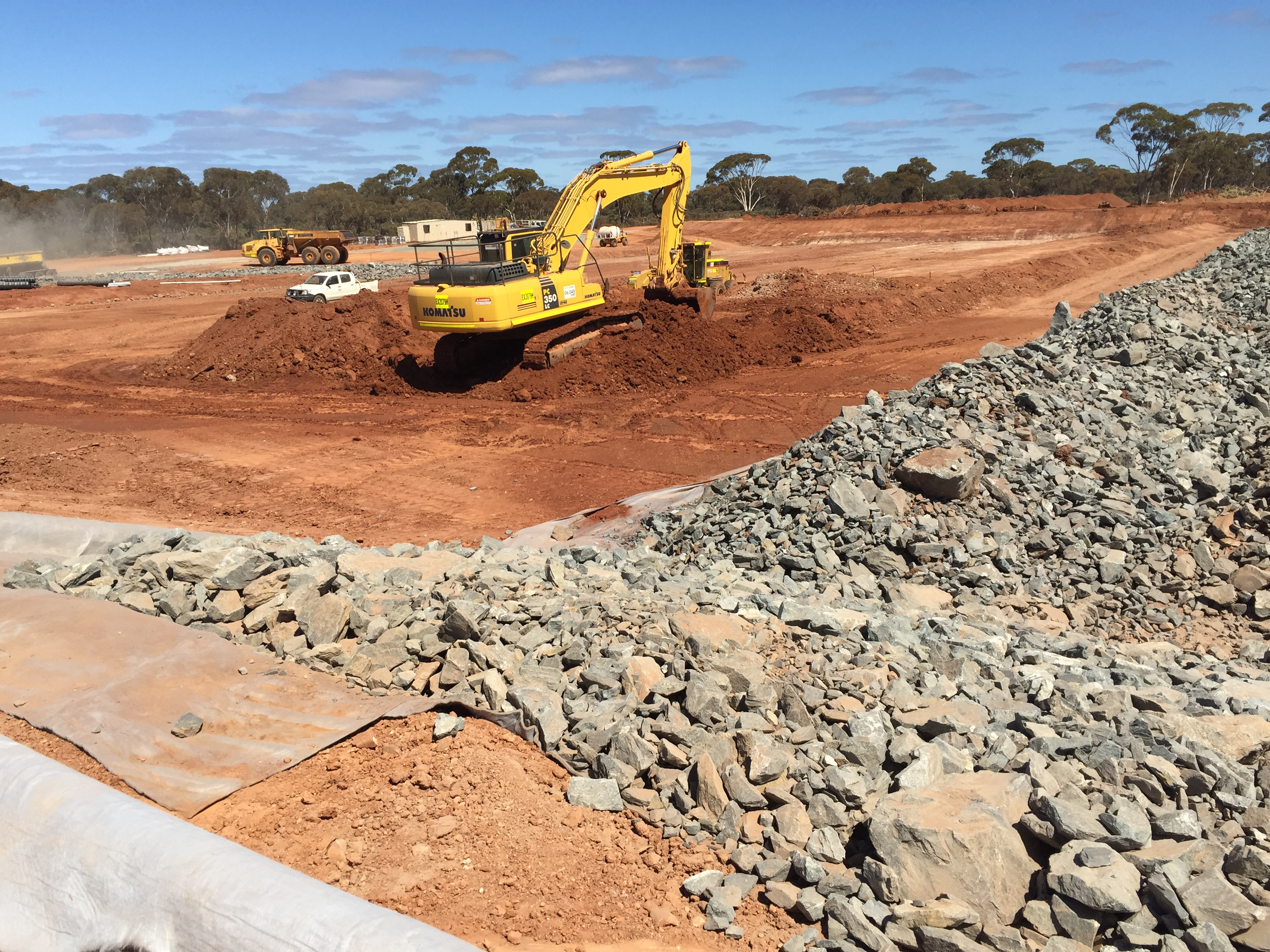 A digger clearing red earth near Kambala WA as part of WML's civil works project.