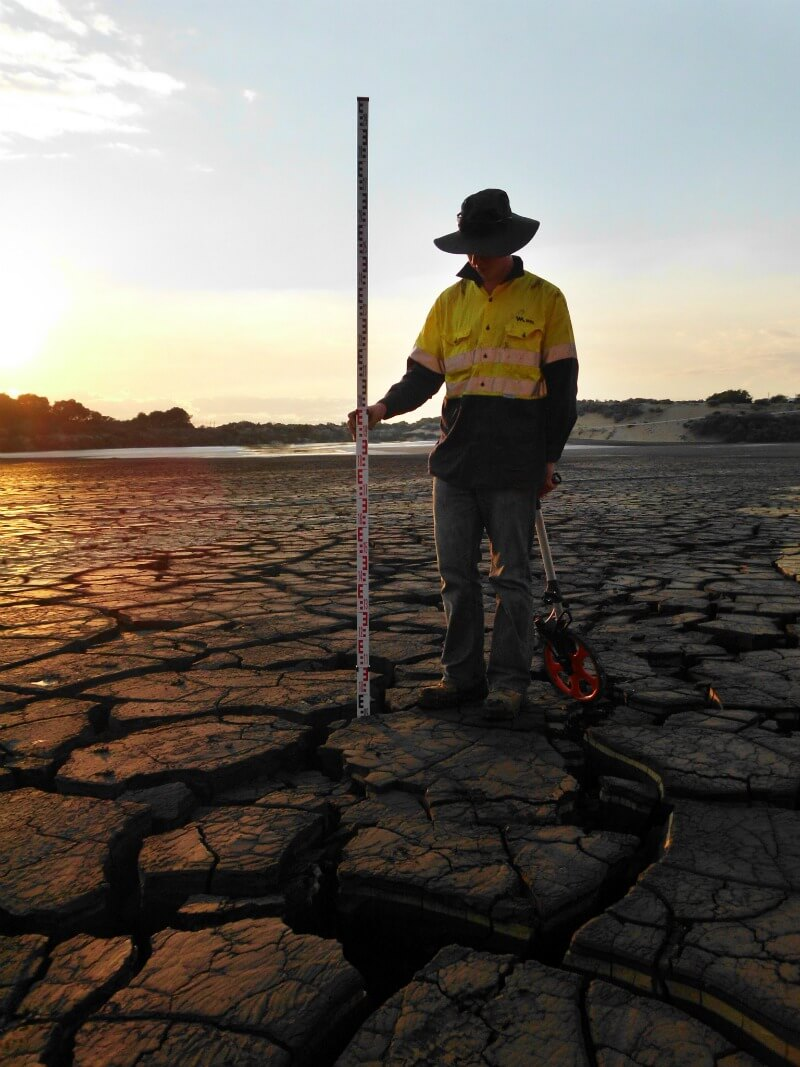 A WML Worker performing geotechnical services including observing the depth of earth cracks at Millennium Chemicals New Tailings Disposal Cell