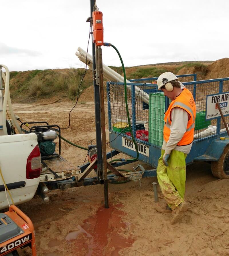 A WML worker drilling into the earth as part of their geotechnical services for Millennium Chemicals' New Tailings Disposal Cell.